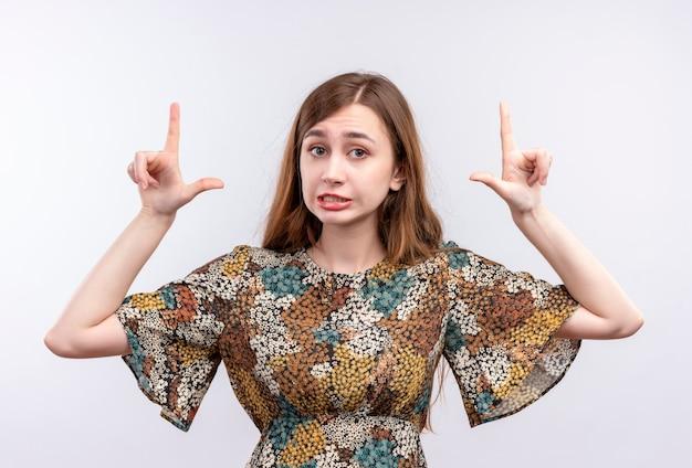 顔に懐疑的な表情で人差し指を指しているカラフルなドレスを着ている長い髪の少女