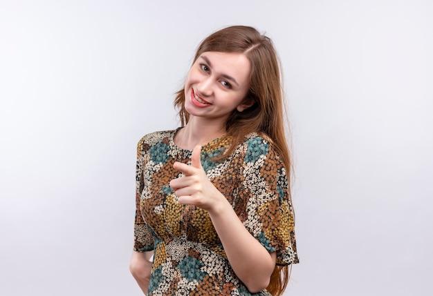 カラフルなドレスを着ている長い髪の少女ポジティブで幸せな人差し指でカメラを指しています