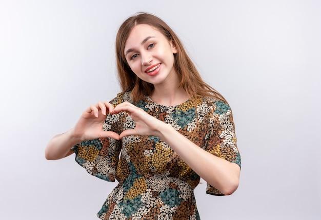Giovane ragazza con i capelli lunghi che indossa un abito colorato sorridente positivo e felice ampiamente facendo il gesto del cuore con la mano sul petto