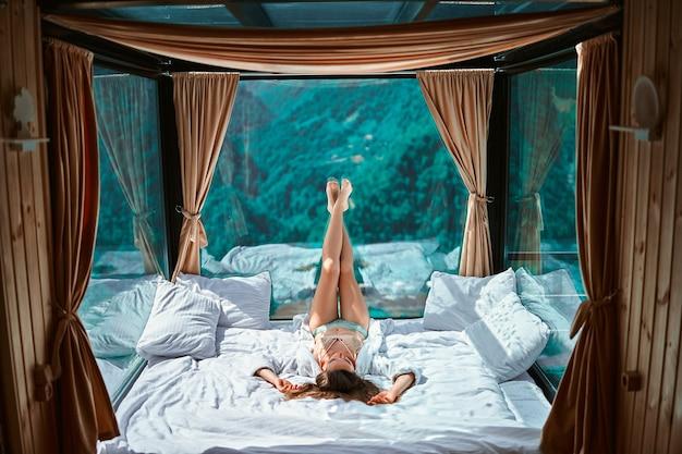 ローブと下着の長い脚を持つ少女は、大きな窓と穏やかな静かな休暇の生活を喜ばせる白い柔らかいベッドに横たわっています