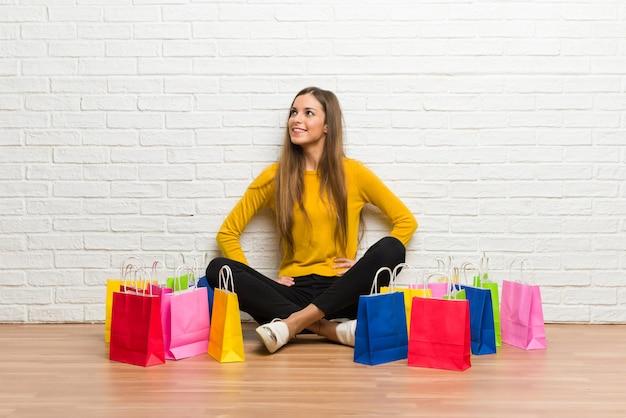 Молодая девушка с много сумок позирует с руки на бедра и смеется