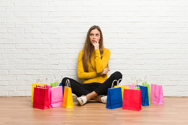 Young girl with lot of shopping bags having doubts while looking up