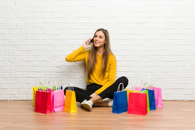 Young girl with lot of shopping bags keeping a conversation with the mobile phone