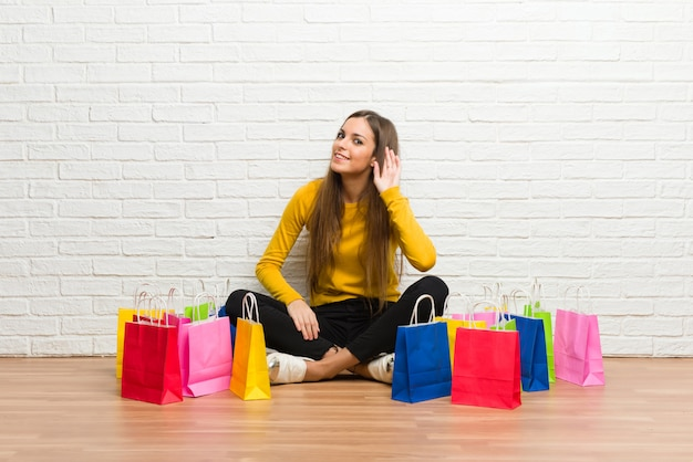 Young girl with lot of shopping bags listening to something by putting hand on the ear