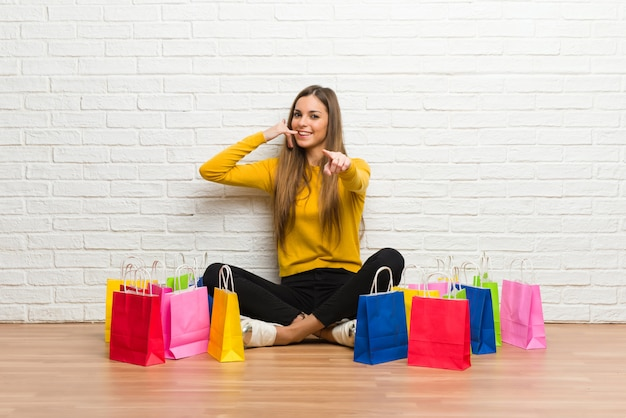Young girl with lot of shopping bags making phone gesture and pointing front