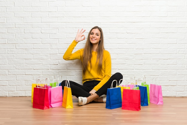Young girl with lot of shopping bags showing an ok sign with fingers