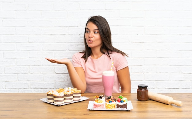 Young girl with lots of different mini cakes holding copyspace imaginary on the palm