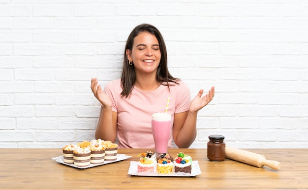 Young girl with lots of different mini cakes laughing