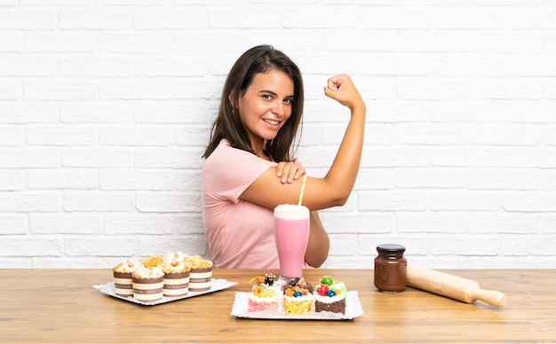 Young girl with lots of different mini cakes making strong gesture