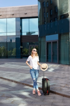 建物の近くで夏に荷物を持つ少女