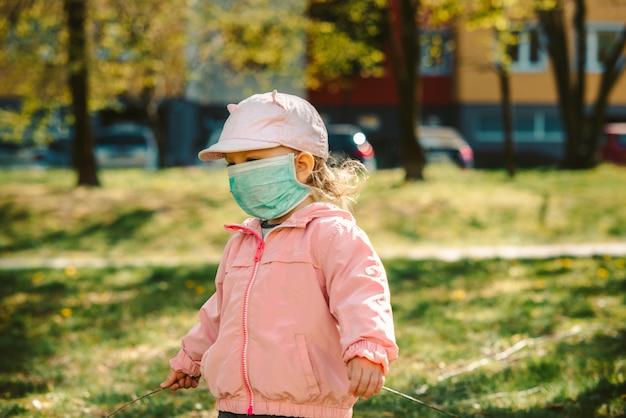 屋外のマスクを持つ少女