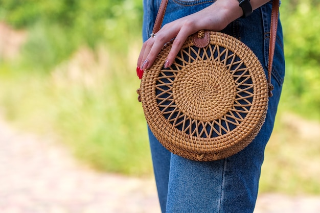 Young girl with modern stylish round straw bag on the nature