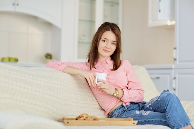 A young girl with a mug of hot drink sits in a bright room.