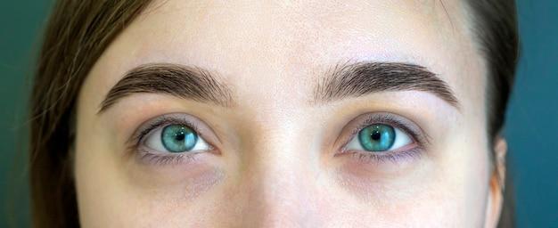 ナチュラルメイクの少女。ビューティーサロンでの眉毛矯正。メイクアップと女性の目のクローズアップショット