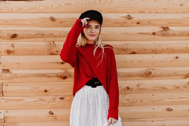 Молодая девушка с естественным макияжем смотрит прямо. прекрасная блондинка в красном свитере и белой юбке выглядит модно.