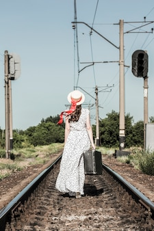 Young girl with old suitcase on the railway tracks.