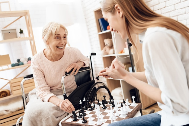 Young girl with old woman play chess at hospital