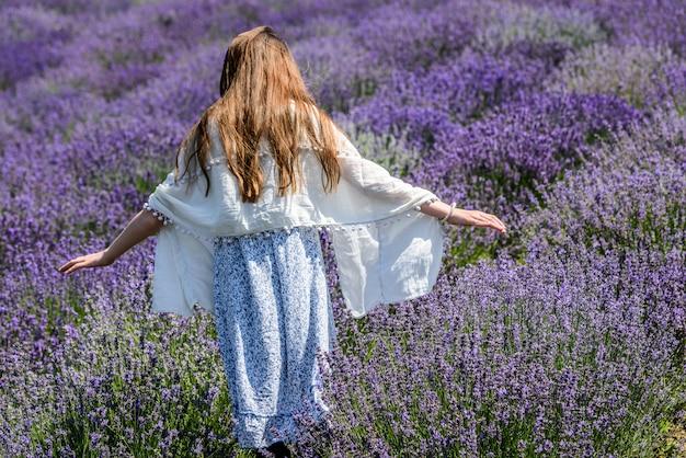 Молодая девушка с распростертыми объятиями наслаждаясь солнцем в лаванде.