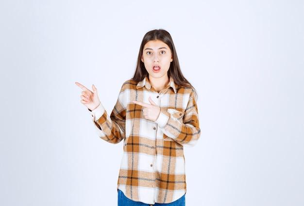 人差し指で離れて指している口を開けた少女。