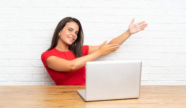 Young girl with pc in a table extending hands to the side for inviting to come