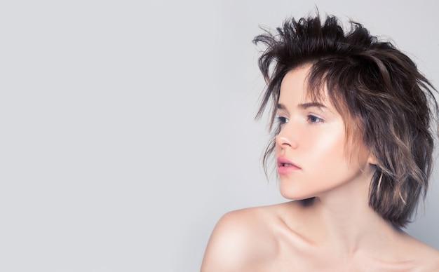 分離された灰色の壁にあなたの製品を提示する側に完璧な肌を持つ若い女の子。自然の美しさはないメイクアップ女性。テキストのモックアップ用の空き容量。スキンケア美容スパトリートメントのコンセプト