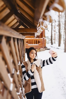 Young girl with phone in waistcoat on against of wooden cottage in winter forest