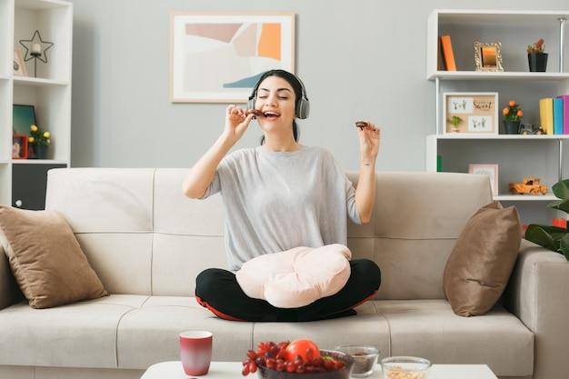 Молодая девушка с подушкой в наушниках ест печенье, сидя на диване за журнальным столиком в гостиной