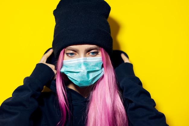 ピンクの髪と青い目をした少女は、医療インフルエンザマスクを身に着けており、黄色の壁に黒いパーカーのセーターとビーニー帽子をかぶっています。