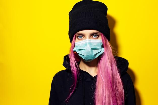 ピンクの髪と青い目をした少女は、医療用インフルエンザマスクを着用し、黄色の壁に黒いパーカーのセーターとビーニー帽子をかぶっています。