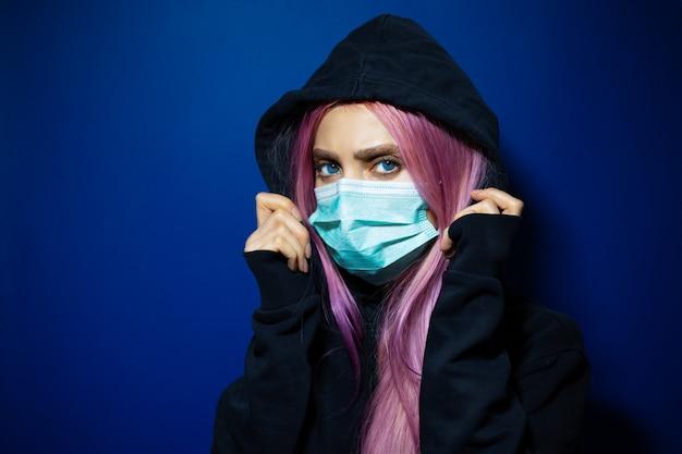 ピンクの髪と青い目をした少女、濃い青色の壁にパーカーのセーターで医療インフルエンザマスクを着用しています。
