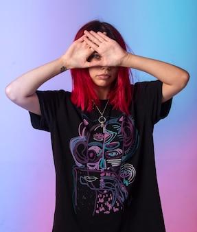 Ragazza giovane con i capelli rosa incrociando le mani sul viso.