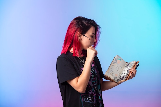 Молодая девушка с розовыми волосами держит альбом для рисования и проверяет его.