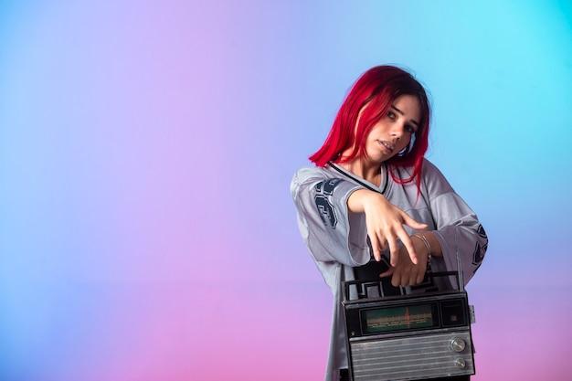 Молодая девушка с розовыми волосами держит старинное радио.