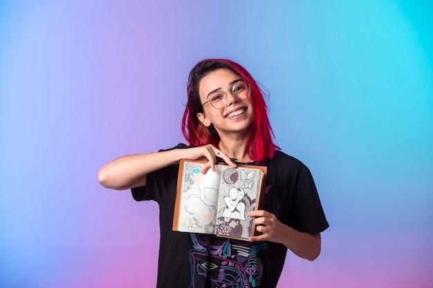 Giovane ragazza con i capelli rosa che tiene un album da disegno e lo dimostra.