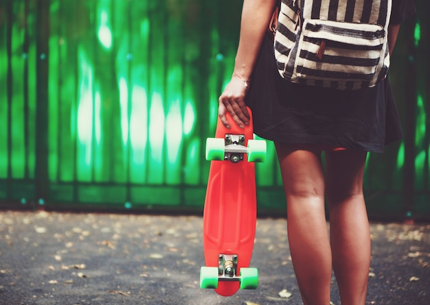 Young girl with plastic orange penny shortboard behind green wall in cap