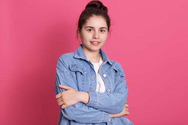 Молодая девушка с приятной внешностью стоит на розовой стене, одевает джинсовую куртку и белую рубашку