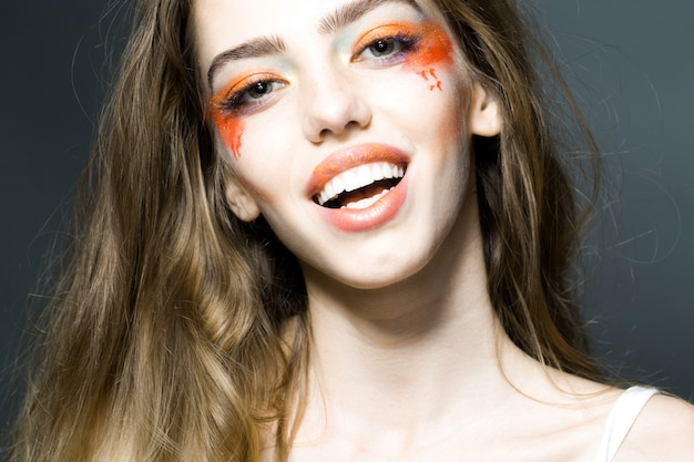 Young girl with pretty smiling face and bright orange makeup in studio closeup