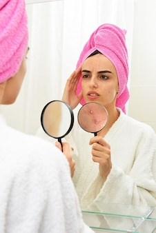 Young girl with problematic skin, holding magnifier over her acne while looking in the mirror