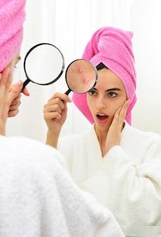 Молодая девушка с проблемной кожей, держащая лупу над прыщами, глядя в зеркало