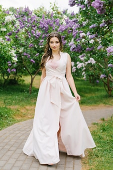 Young girl with professional makeup plus size in a blooming lilac garden in a beautiful long pink dress
