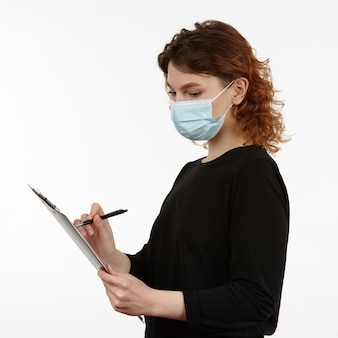 Young girl with a protective mask on her face with a notebook and a pen in her hands.