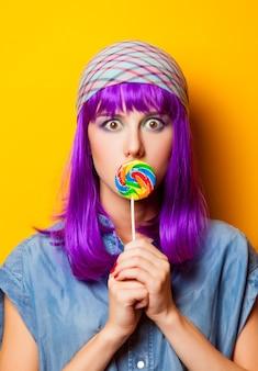 Молодая девушка с фиолетовыми волосами и леденцом на желтом