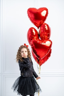 Young girl with red air balloons