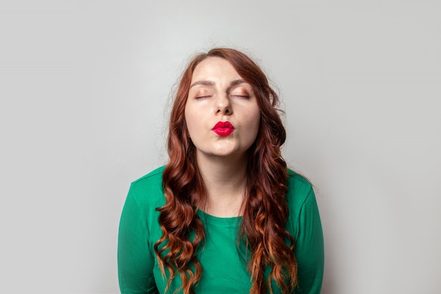 Young girl with red curly hair and red lipstick giving a kiss on a gray wall background
