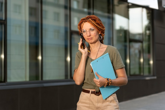 빨간 향취를 가진 어린 소녀가 동료와 전화를 하고 있습니다. 디지털 에이전시 비정규직
