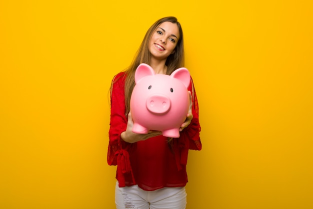 Young girl with red dress over yellow wall holding a piggybank