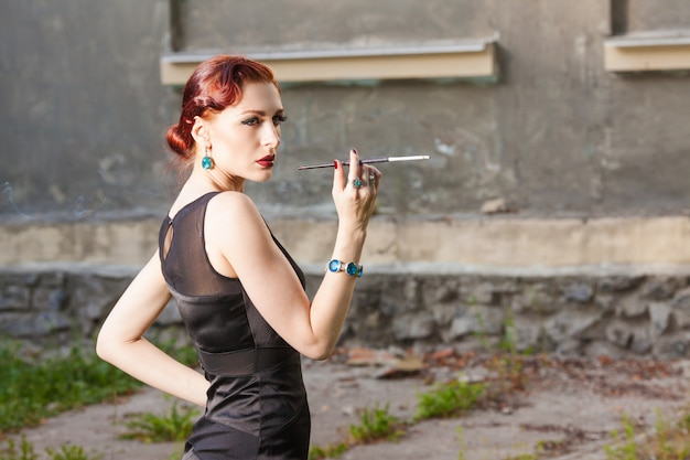 Young girl with red hair in black dress smokes cigarette in the mouthpiece