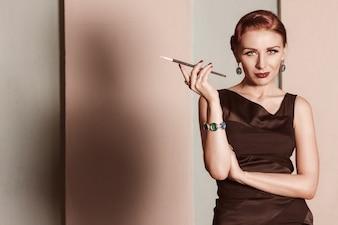 黒のドレスで赤い髪の少女はマウスピースでタバコを吸う