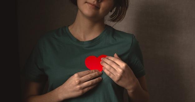 Молодая девушка с красным сердцем. счастливый подросток, дающий свою любовь концепции баннера фото