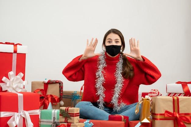 빨간 스웨터와 검은 마스크와 어린 소녀 주위에 앉아 누군가를 호출 화이트 선물